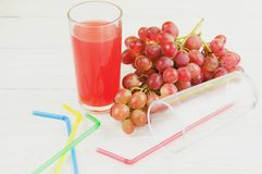 Bunch of fresh ripe rose grapes near transparent and fragile glass full of juice beside empty glass with plastic tubule. And heap of colored tubules on old stock image