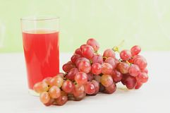 Bunch of fresh ripe rose grapes near transparent and fragile glass full of juice on old wooden white planks. Bunch of fresh ripe rose grapes near transparent and stock photo
