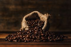 Bunch of fresh roasted coffee beans with burlap sack on a wooden table. Agriculture and drink concept Stock Photo