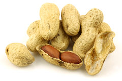 A bunch of fresh roasted peanuts and a peeled one Royalty Free Stock Image