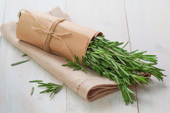 Bunch of fresh rosemary and napkin. On wooden table Stock Photography