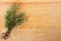 Bunch of fresh rosemary on an old wooden chopping board Royalty Free Stock Photo