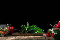 Bunch of fresh spinach with various vegetables on wooden table. Bunch of fresh spinach with various vegetables on a wooden table. Concept of cooking healthy food Stock Photography