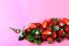 Bunch fresh strawberry fruits at the bottom, chocolate candies, white flower on pink background with copy space. View from above, stock image