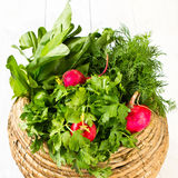 A bunch of fresh vegetables in basket. A bunch of fresh different vegetables in a bowl wicker basket on white wooden background Stock Image