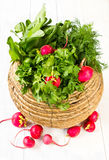 A bunch of fresh vegetables in a bowl wicker basket on white woo. A bunch of fresh different vegetables in a bowl wicker basket on white wooden background Stock Images