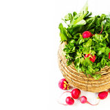 A bunch of fresh vegetables in a bowl wicker basket on white woo. A bunch of fresh different vegetables in a bowl wicker basket on white wooden background Stock Photo