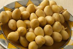 Bunch of fresh yellow dates. On a mediterranean dish Royalty Free Stock Images