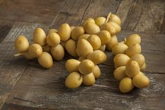 Bunch of fresh yellow dates. On the table Stock Photography