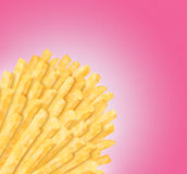 Bunch of fries. In corner on smooth pink background. Clipping path of fries is included Stock Image