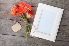 Bunch of gerbera flowers and photo frame Stock Images