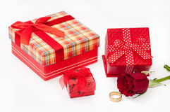 Bunch of gifts with red rose and golden ring Stock Photos