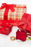 Bunch of gifts with red rose and golden ring Stock Image
