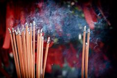A bunch of glowing incense sticks stock photo