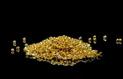 A bunch of gold grains. Isolated on a black. Background stock photos