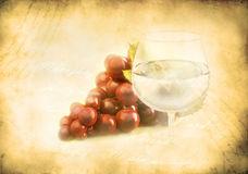 A bunch of grape and wineglass. On an ancient background Stock Image