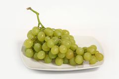Bunch of grapes. A bunch of fresh green grapes on a plate isolated on white studio background royalty free stock photos