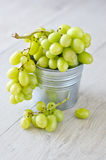 Bunch of grapes in a bucket. Wooden background Stock Image