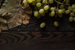 Bunch of grapes, dry leaves on the dark wooden surface Royalty Free Stock Image