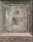 Bunch of grapes embossed in an old bronze door. Stock Image