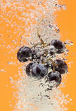 Bunch of grapes floating in water with air bubbles Royalty Free Stock Photography
