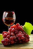 Bunch of grapes and glass of wine. Bunch of grapes and glass of wine on a black background Royalty Free Stock Photos
