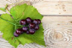 Bunch of grapes. Bunch of green grapes and grape leaves on a wooden table Royalty Free Stock Images