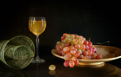A bunch of grapes lying on a round wooden plate next to a glass of white wine standing on background with reflection Stock Images