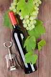 Bunch of grapes, red wine bottle and corkscrew Stock Photos