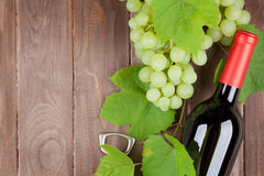 Bunch of grapes, red wine bottle Stock Images