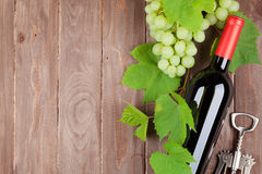 Bunch of grapes, red wine bottle and corkscrew Stock Image