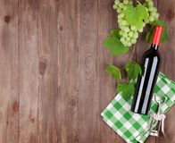 Bunch of grapes, red wine bottle Stock Photos