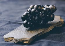 Bunch of grapes on a stone. Bunch of grapes on a stone with a cloth background stock image