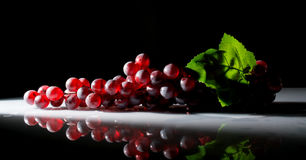 Bunch of grapes in the sun on a dark Stock Photo