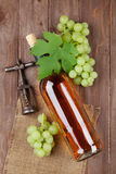 Bunch of grapes, white wine bottle and corkscrew. On wooden table background stock images