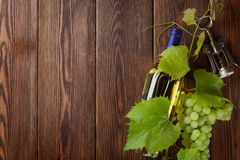Bunch of grapes, white wine bottle and corkscrew. On wooden table background with copy space stock photography