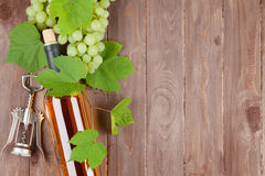 Bunch of grapes, white wine bottle and corkscrew. On wooden table background with copy space royalty free stock photo