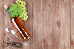 Bunch of grapes, white wine bottle and corkscrew. On wooden table background with copy space royalty free stock image