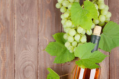 Bunch of grapes and white wine bottle. On wooden table background with copy space stock images