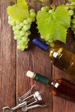 Bunch of grapes, white wine bottles and corkscrew. On wooden table royalty free stock image