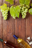 Bunch of grapes, white wine bottles and corkscrew. On wooden table background with copy space stock photos