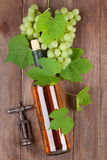 Bunch of grapes, white wine and corkscew. Bunch of grapes, white wine bottle and corkscrew on wooden table background royalty free stock images