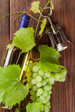 Bunch of grapes, white wine and corkscrew. Bunch of grapes, white wine bottle and corkscrew on wooden table background royalty free stock photography