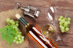 Bunch of grapes, white wine and corkscrew. On wooden table background stock images