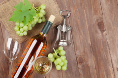 Bunch of grapes, white wine and corkscrew. On wooden table background with copy space royalty free stock photo