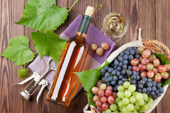 Bunch of grapes, white wine and corkscrew. On wooden table background. Top view royalty free stock photos