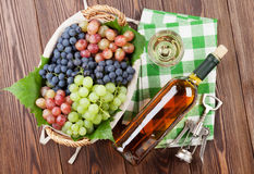 Bunch of grapes, white wine and corkscrew. On wooden table background. Top view stock photos