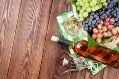 Bunch of grapes, white wine and corkscrew. On wooden table background. Top view with copy space stock photo