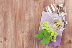 Bunch of grapes, white wine and corkscrew. On wooden table background. Top view with copy space stock image