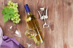 Bunch of grapes, white wine and corkscrew. On wooden table background. Top view with copy space royalty free stock images